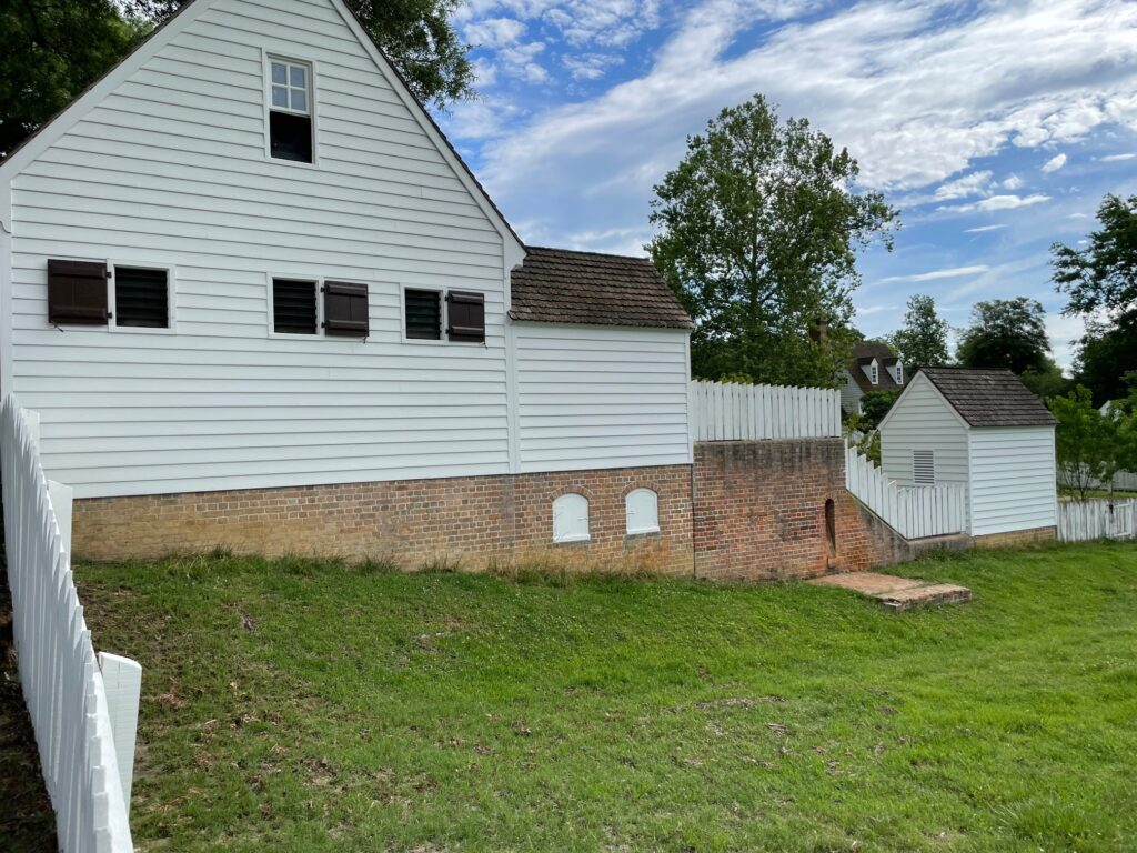 Side of a white building with brick foundation and a grassy lawn in Colonial Williamsburg