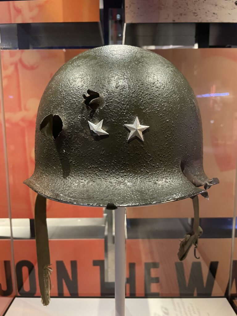 photo of a a single mutilated helmet once worn by Major General Maurice Rose, which shows the entry and exit holes of the bullets that ended his life.