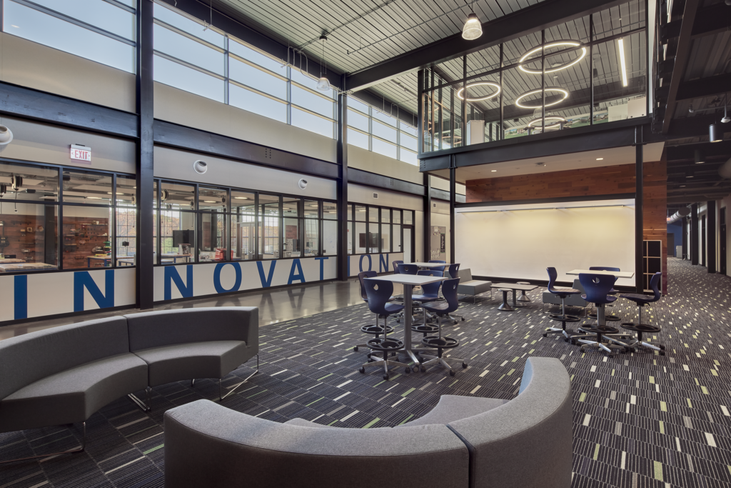 Photograph of Innovation center with blue letter in wall and tables and chairs in the foreground