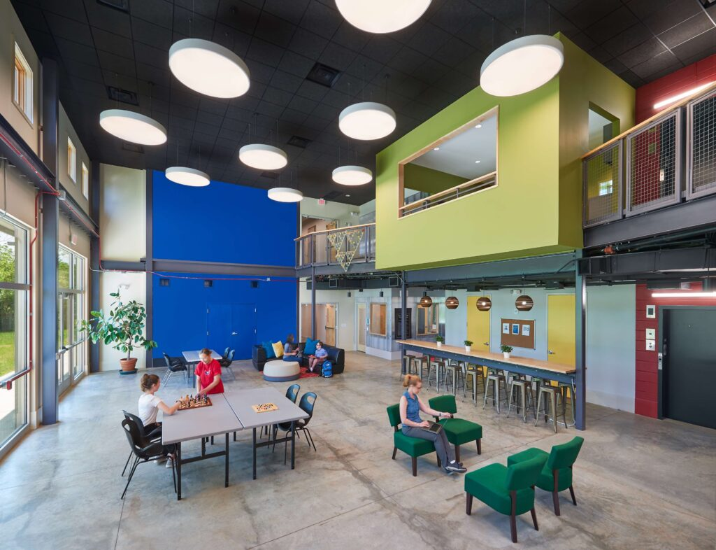 Brightly colored blue and yellow flexible classroom space with tables and work spaces.
